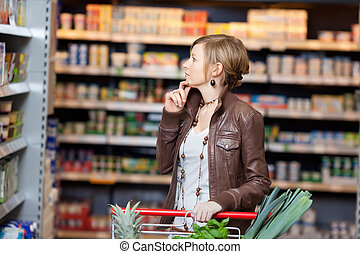Thoughtful Woman Looking At Products In Supermarket