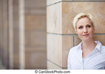 Thoughtful Woman Looking Away While Leaning On Pillar