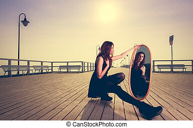 thoughtful woman looks at reflection in mirror - Solitude ...
