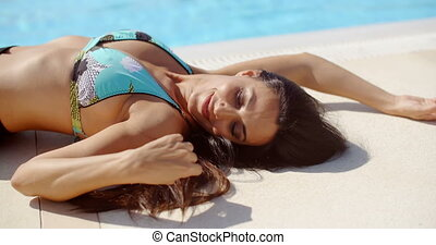 Thoughtful Woman Lying Down at the Poolside