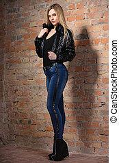 thoughtful woman posing near a brick wall