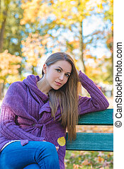 Thoughtful woman relaxing in an autumn park sitting on a...