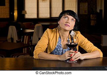 Thoughtful woman sitting at the bar