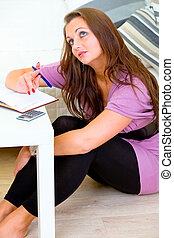 Thoughtful woman sitting on floor at home and making notes in diary