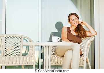 Thoughtful woman sitting on terrace