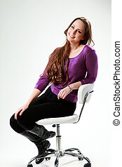 Thoughtful woman sitting on the chair over gray background