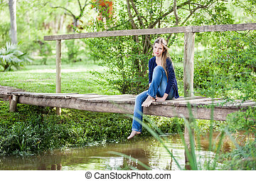 Thoughtful Woman Sitting On Wooden Bridge