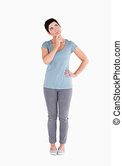 Thoughtful woman standing up against a white background