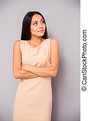Thoughtful woman standing with arms folded