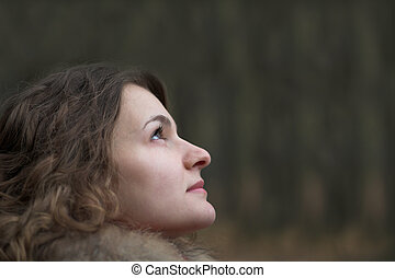 Thoughtful young woman with curly haur in autumn park