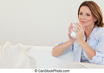 Thoughtful woman with cup of coffee on sofa