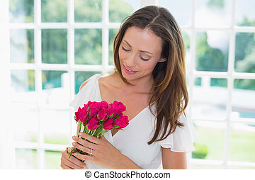 Thoughtful woman with flowers at home