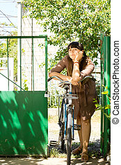 Thoughtful woman with her bicycle