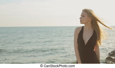 Thoughtful woman with long hair wearing a long black dress standing on a rock by the sea at sunset and thinking