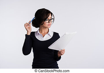 Thoughtful woman with papers standing isolated on a white background