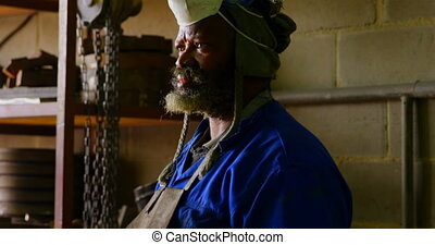Thoughtful worker standing in foundry workshop 4k - ...