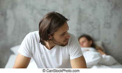 Thoughtful worried man sitting on bed, sleeping woman at background