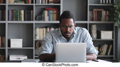Thoughtful young african american man in eyeglasses watching educational lecture online on computer, writing notes on paper, web surfing searching additional information in internet, sitting at home.