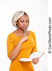Thoughtful young african american woman thinking and writing in notebook