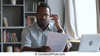 Thoughtful young african man looking through reading paper document, feeling stressed about banking loan money debt notification. Depressed biracial guy frustrated about high bills, dismissal notice.