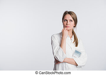 Thoughtful, Young Asian female doctor looking away isolated on white background