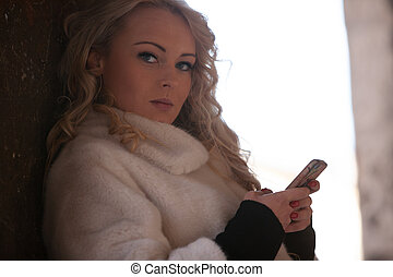 Thoughtful young blond woman glancing sideways at the camera...
