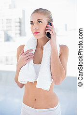 Thoughtful young blonde model calling with her mobile phone