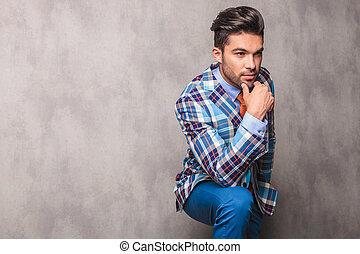 Thoughtful young business man leaning his hand on his leg