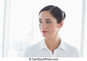 Thoughtful young business woman looking away