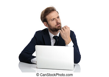thoughtful young businessman in navy blue suit looking to ...