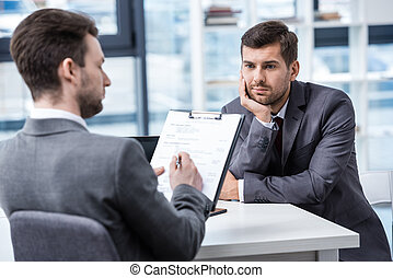Thoughtful young businessman looking at manager with clipboard at job interview, business concept