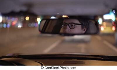 Thoughtful young businessman s face in a rear view mirror, driving a car at night