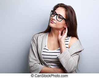 Thoughtful young casual woman looking on empty copy space