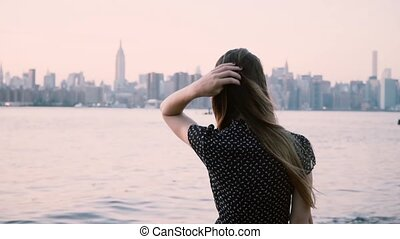 Thoughtful young Caucasian girl with hair blowing in the wind watching sunset at New York City river shore slow motion.