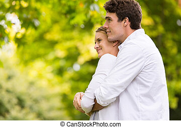 thoughtful young couple hugging outdoors