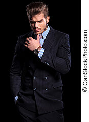 thoughtful young fashion model in suit and tie