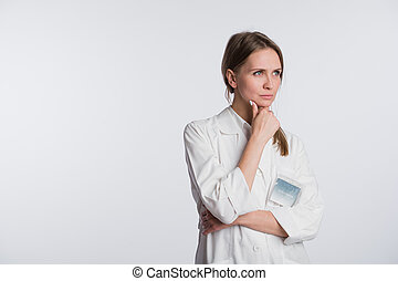 Thoughtful, Young female doctor looking away isolated on white background