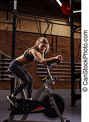thoughtful young female is sitting on the exercise bike