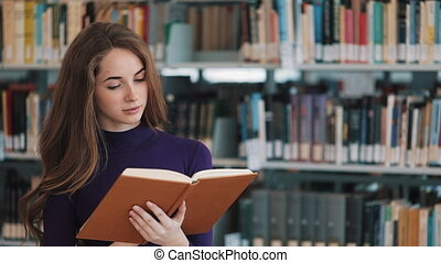 Thoughtful young female student reads a book standing in the library