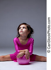 Thoughtful young girl posing with gymnastic ball