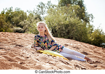 Thoughtful young girl resting on beach