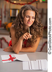 Thoughtful young housewife signing christmas postcards in...