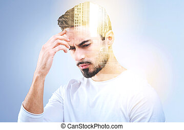 Thoughtful young man holding his forehead