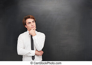 Thoughtful young man on chalkboard background