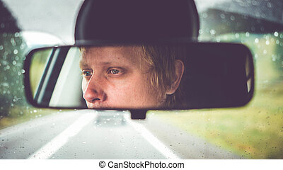 Thoughtful young man riding in car through mountains during rainy day