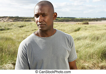 Thoughtful Young Man Standing On Beach Amongst Dunes