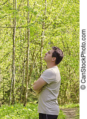 Thoughtful young man with crossed arms standing in the forest on sunny spring day.