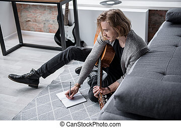 Pensive young male musician is composing new song in his apartment. He is sitting on carpet and noting words into the writing-pad. Inspiration concept