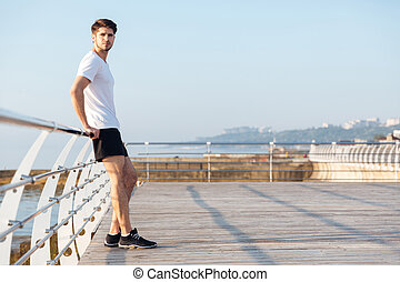 Thoughtful young sportsman standing outdoors and thinking -...