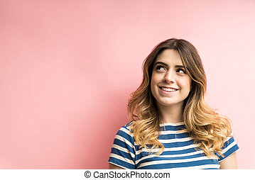 Thoughtful Young Woman Against Plain Background In Studio
